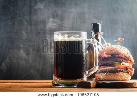 Glass of dark beer with bottle and burger on a chalk board background