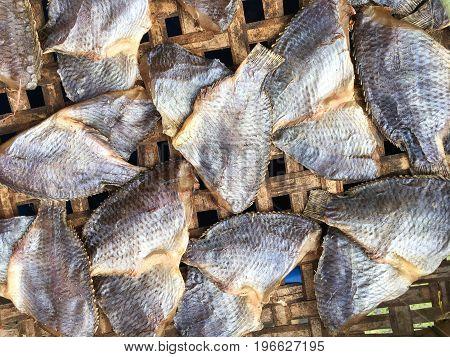 dry salty nile tilapia fish on bamboo floor