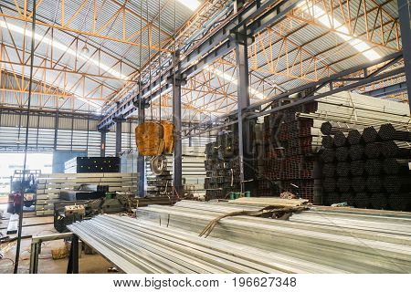 lifting crane with yellow hook in steel pipe warehouse