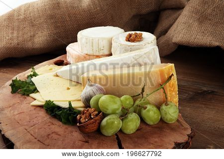 Cheese Platter With Different Cheese On Brown Wooden Plate