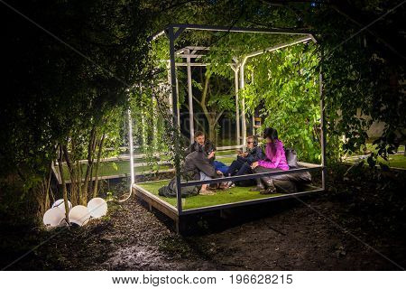 People Relaxing In A Special Chilling Natural Area Decorated With Small Led Lamps
