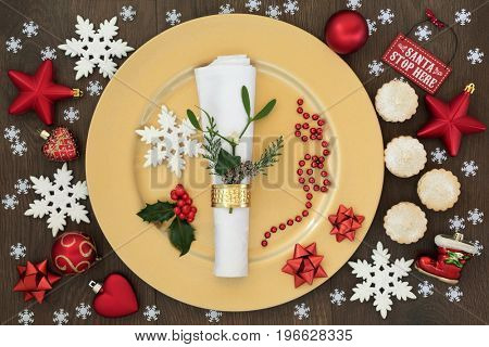 Christmas dinner place setting with gold plate, napkin and ring with mistletoe and cedar leaf sprig, holly, snowflake and red bauble decorations with mince pies on oak table background.