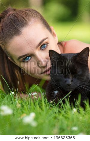 Beautiful female teenager girl young woman with blue eyes, laying down outside on grass with a black cat