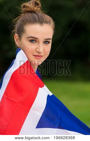 Pretty teenage girl female young woman outside in summer wrapped in a British Union Jack flag at a party, music festival or concert