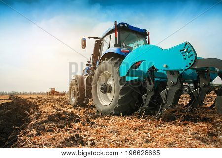 A modern tractor with a trailed plow on the field on a sunny day. The concept of work in a fields and agriculture industry.