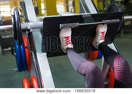 Active young woman doing exercise for legs on special equipment in gym