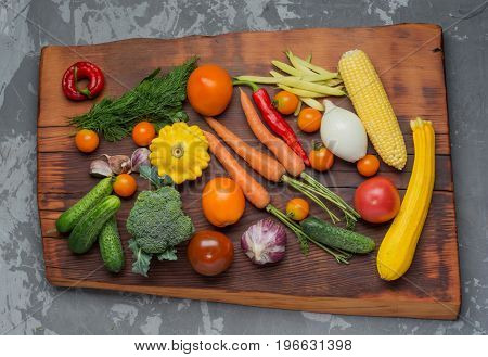 Fresh ripe garden vegetables cooking on wooden table. Top view