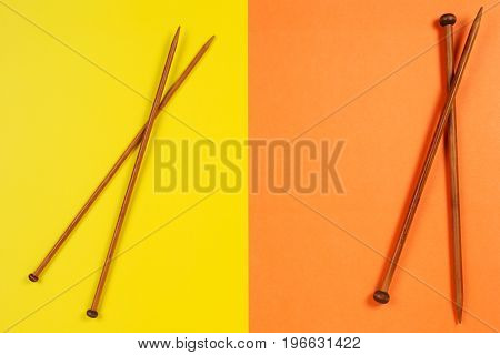 Wooden knitting needles on colorful yellow and orange background