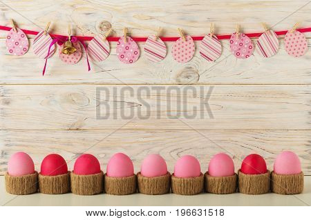 Easter eggs and Easter decor paper eggs with a pink ribbon on a light wooden background. Selective focus.