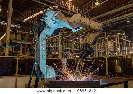 Industrial robot is test run new program in automotive factory