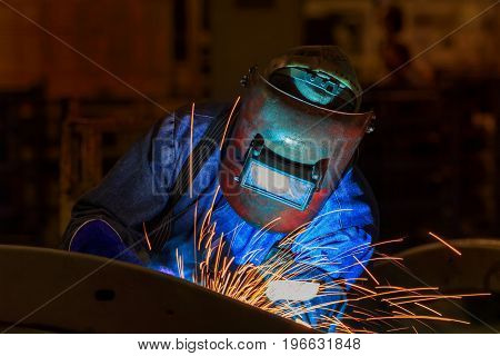 Industrial worker with protective mask is welding metal .