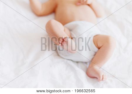 Baby's feet. Little child wearing white bodysuit and diaper. Cozy morning bedtime at home.
