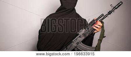 Woman holding an automatic weapon. Concept of war