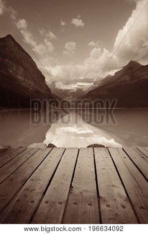 Lake Louise with pier at sunrise in Banff national park with mountains and forest in Canada.