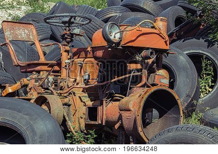 Old rusty red vintage tractor in a farm with used tires