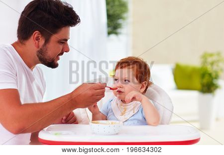 funny toddler baby looking suspiciously on father during a meal