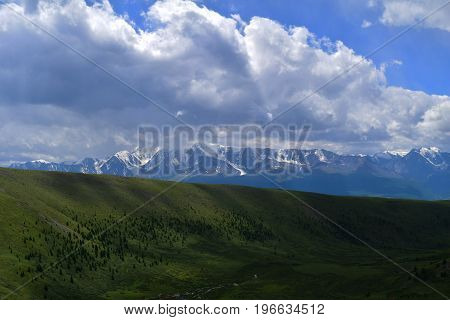 Landscape of snow peaks of North-Chuyski ridge and hills with green meadows in Altai mountains in overcast weather. Aktash Altay Republic Russia.