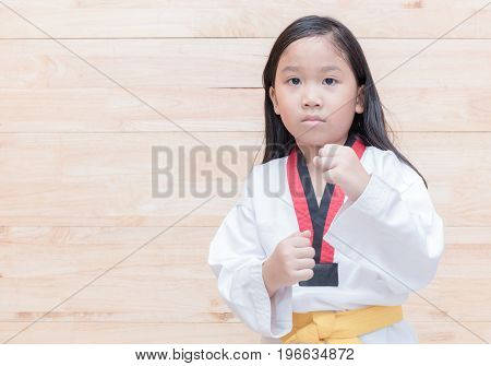 Asian taekwondo girl on acton on wood background sport and healthy concept
