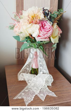 Wedding bouquet with lace ribbon bride's traditional symbolic accessory. Floral composition with peonies and roses.