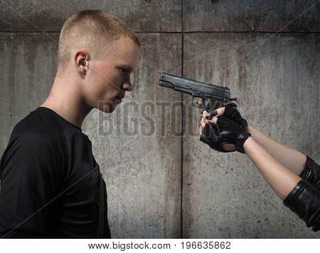 Young man. Female hand pointing the gun in the forehead the man