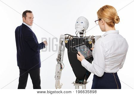 How did the test go. Clever admirable inspired man testing his robot using interactive screen computer while his colleague tracking down the data