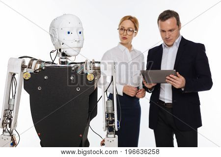 Latest development. Talented strategic savvy colleagues working on modern lab and applying some settings to their invention while standing isolated on white background