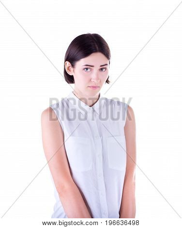 A beautiful, sweet and shy girl with short dark brown hair and an elegant white blouse isolated on a white background. A charming and young woman is feeling guilty. Negative emotion, facial expression