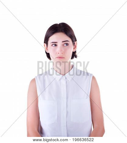 Close-up portrait of an emotional, sad and mysterious young woman, isolated on a white background. A charming and thoughtful girl in a white blouse and with short dark hair has something in mind.