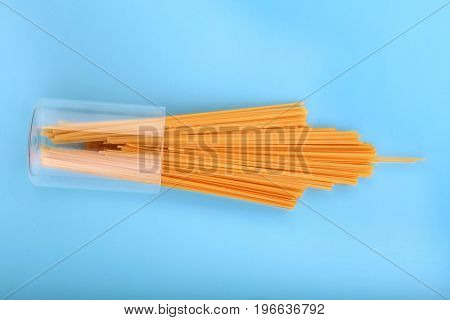 A transparent and inverted glass with uncooked pasta on a bright blue background. Raw and fresh flour products. Bright yellow dry spaghetti. Raw spaghetti in a huge glass.