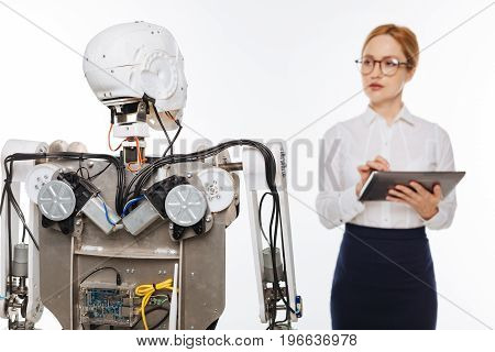 Running tests. Diligent observant scrupulous woman trying out different algorithms while experimenting in a lab and developing artificial intelligence