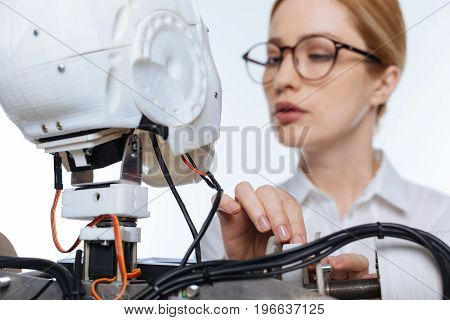 Careful look. Serious young penitent woman making sure the system functioning right while testing the robot in a lab