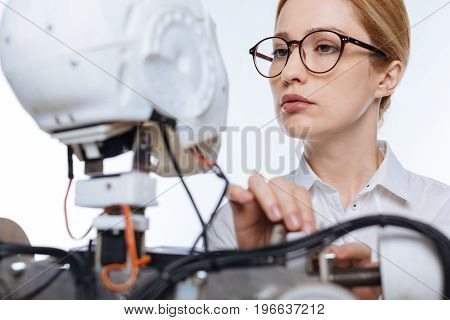 Robotic engineering. Attentive encouraging committed scientist developing ambitious project while fixing up the wires of the robot and running an experiment