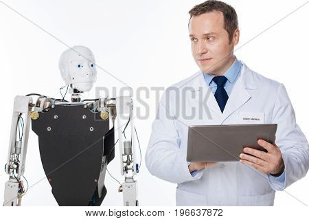 Technological examinations. Handsome inspired progressive man working in the lab and developing software for robots while testing it on the mechanism itself