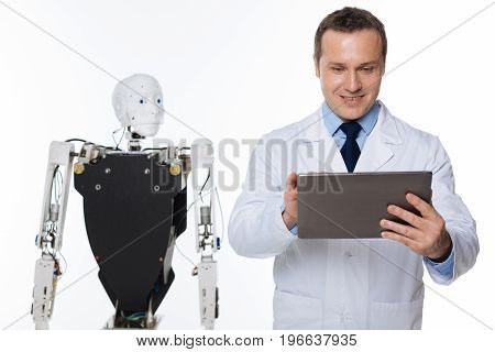 Successful tests. Optimistic dedicated talented man running an experiment and receiving the empirical data while standing isolated on white background