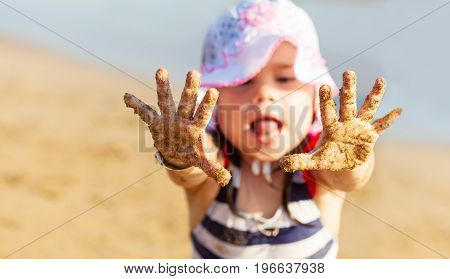 Little girl showing her hands with sand on the palms