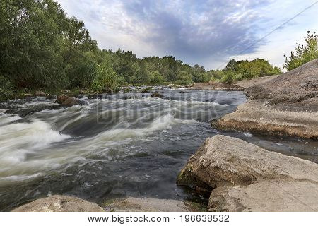 The river Southern Bug in the summer - rocky shores rapids fast river flow bright green vegetation and a cloudy blue sky