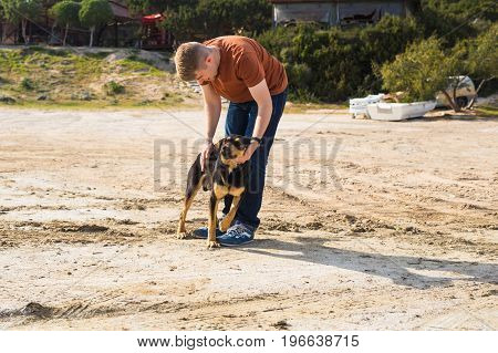 pet, domestic animal, season and people concept - happy man with his dog walking outdoors.