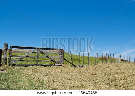 Old wooden timber gate and fence in a field in rural New Zealand NZ with blue sky and copy space