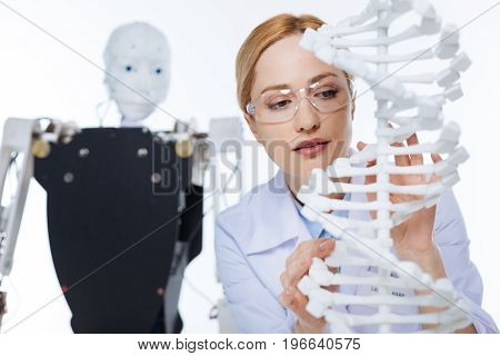 Careful study. Enthusiastic devoted motivated woman working in a lab and developing new scientific project while examining the model of a genome molecule