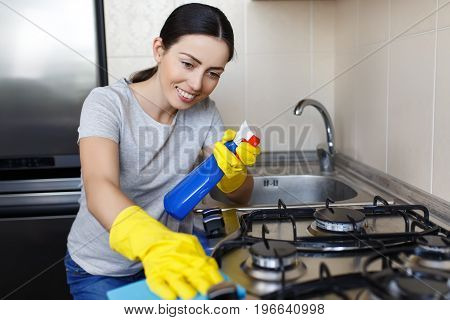 young smiling woman in protective glove with rag cleaning stove. Girl polishing kitchen. People, housework, housekeeping, cleaning concept