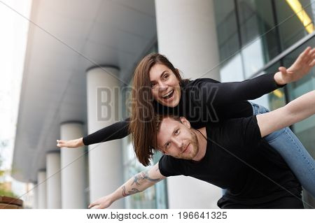 Happy Caucasian couple having fun outdoors. Bearded attractive young male giving a piggyback ride to his cheerful excited cute girlfriend both keeping arms stretched posing in urban setting