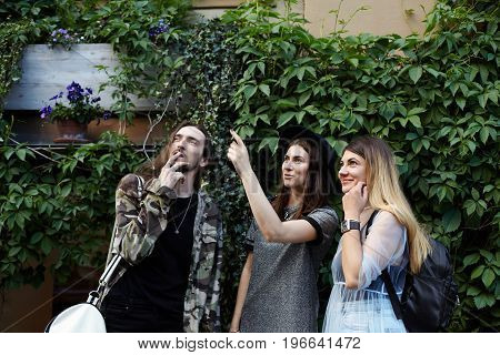 People friendship summer holidays and tourism concept. Three stylish teenagers standing at green wall and pointing index fingers up looking excited while having walk in resort town during vacations
