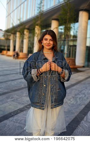 People youth modern urban lifestyle fashion and style concept. Happy stylish teenage girl wearing trendy accessories and denim jacket over elegant dress standing in cityscape smiling at camera