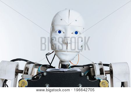 Human like. White elaborate modern highly technological mechanism with artificial intelligence standing isolated on white background