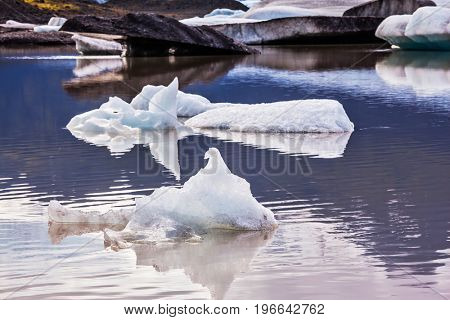 The concept of extreme northern tourism. Summer in Iceland. The cold lake with splinters of ice floes formed by thawed snow of glacier Vatnajokull