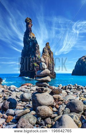 Stone pyramid - troll on a pebble beach. Volcanic island of Madeira in the Atlantic Ocean. Three huge scenic rocks. Concept of exotic and ecological tourism