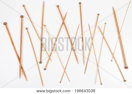Wooden bamboo knitting needles in different sizes on white background. Top view