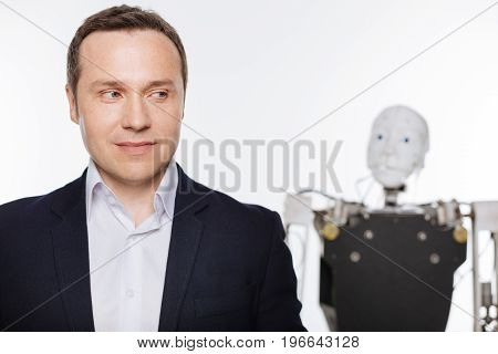 Almost the same. Handsome delighted passionate man developing artificial intelligence while testing it on a robot and standing isolated on white background