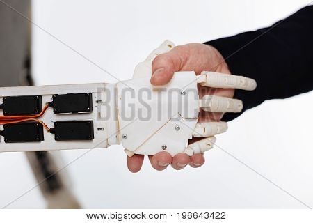 Handshake with future. Classy diligent intellectual scientist running an experiment in a lab and checking the mechanism of response while standing isolated on white background