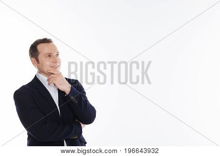 Standard pose. Handsome vibrant enthusiastic guy standing isolated on white background and seeming very interested while holding his chin